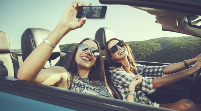 Two young women taking selfe with a smartphone in a convertible car